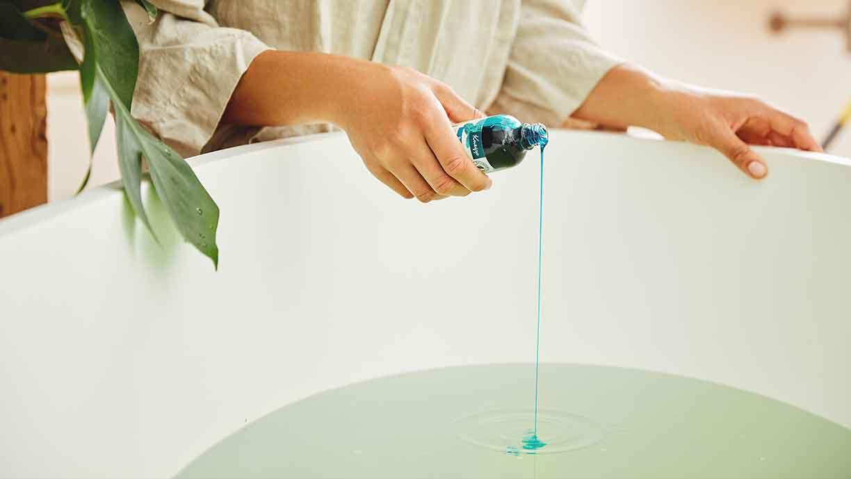 Frau gießt Badeöl in die Wanne