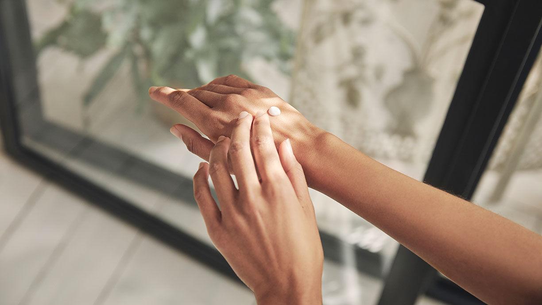 Frau cremt sich die Hände ein