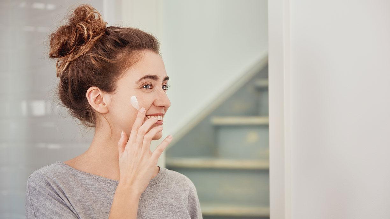 Lächelnde Frau cremt sich das Gesicht ein