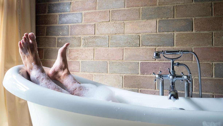 Männerbeine in der Badewanne