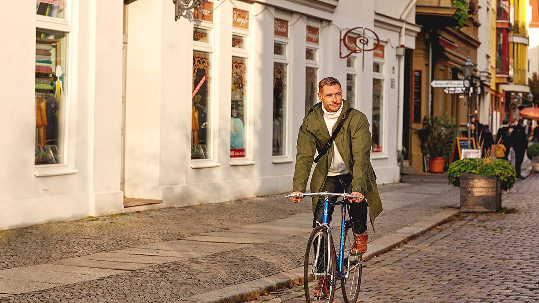 Fahrradfahrender Mann in der Fußgängerzone