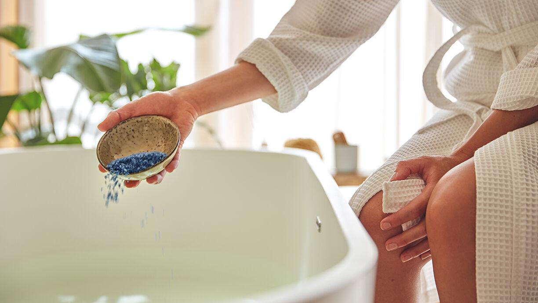 Frau schüttet Badesalz in die Wanne