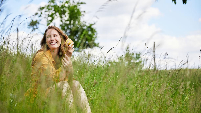 glückliche Frau sitzt in der Natur