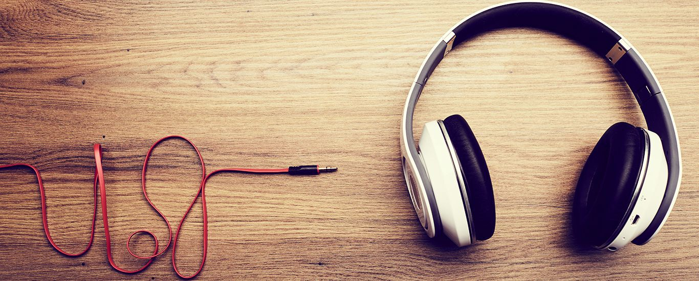 Kopfhörer und Kabel auf einem Holztisch.