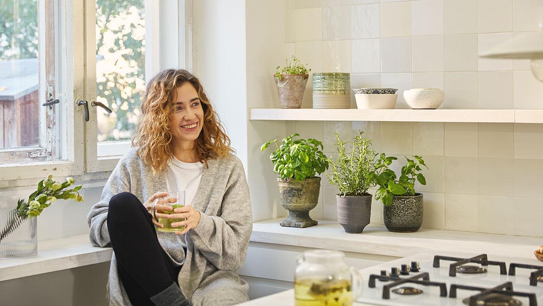 Frau trinkt Tee in der Küche