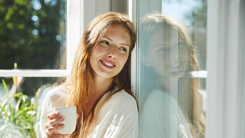 Frau entspannt sich bei einer Tasse Tee am Fenster