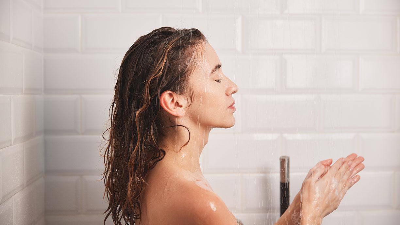 entspannte Frau unter der Dusche