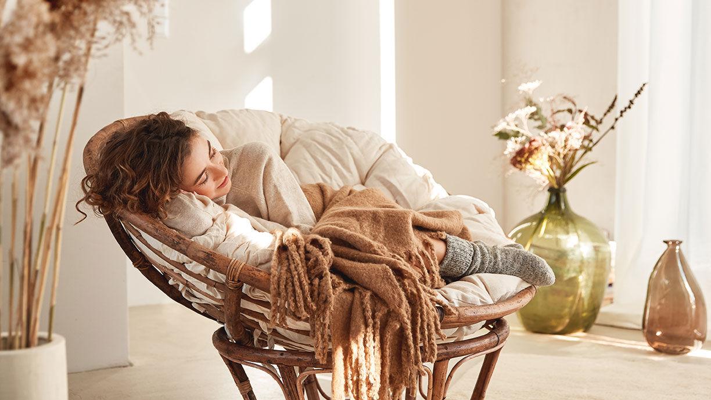Frau liegt in einem kuscheligen Sessel