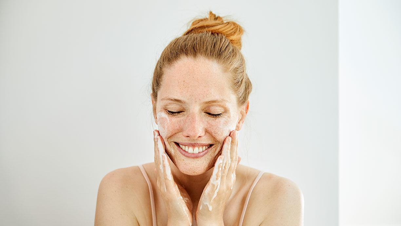 lachende Frau wäscht sich ihr Gesicht