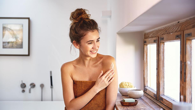 lachende Frau cremt ihren Arm ein