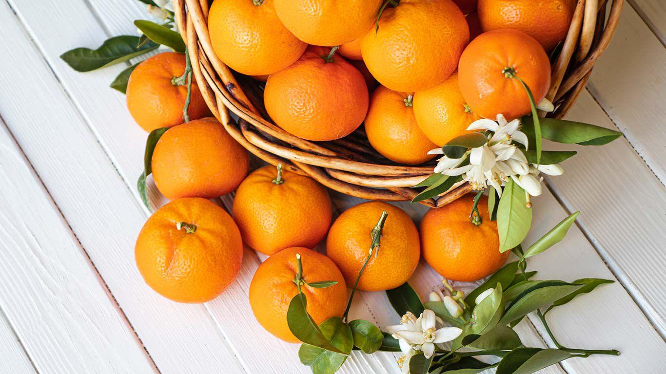 Mandarinen in einem Korb auf weißem Holztisch