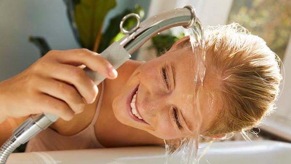 Blonde Frau führt Gesichtsguss über der Badewanne aus.