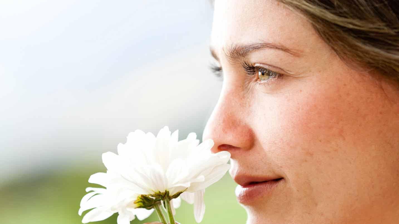 Frau riecht an einer Blüte