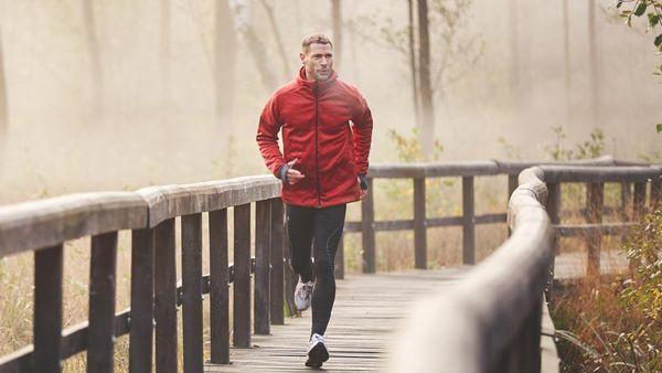 Mann joggt im Morgennebel in roter Jacke über einen Steg.