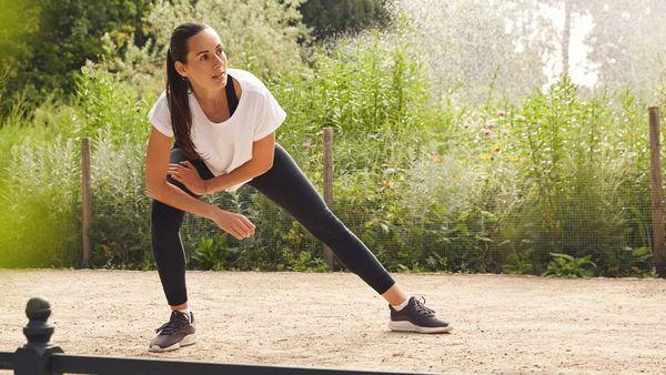 Frau in Sportklamotten dehnt ihre Beine auf einem Waldweg.