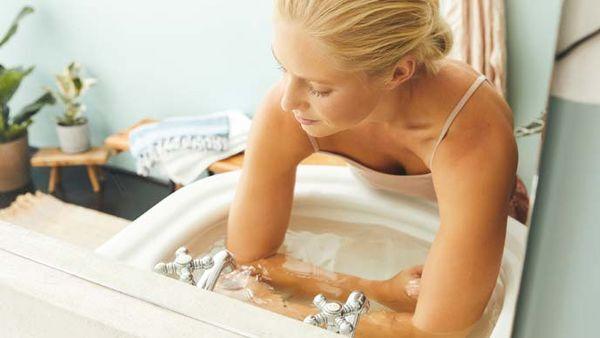 Blonde Frau führt im Handwaschbecken ein kaltes Armbad durch.