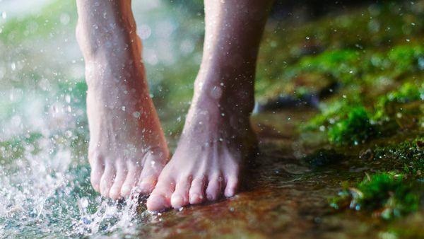 Nahaufnahme von Füßen auf einer moosigen Oberfläche. Wasserspritzer im linken Bildrand.