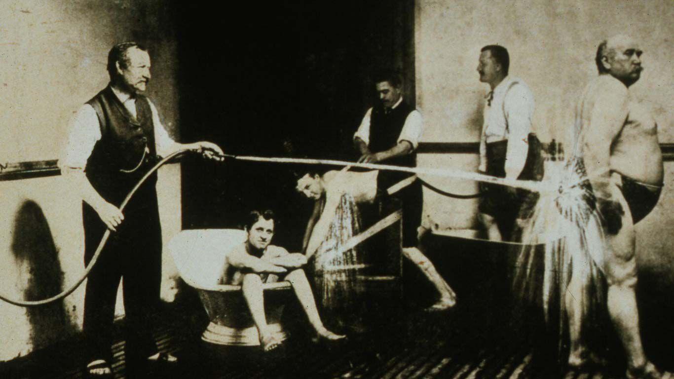 Schwarzweiß-Foto einer Badeanstalt des 19. Jahrhunderts: Einige Männer erhalten einen Kneipp-Guss.