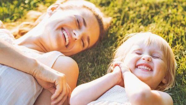 Mutter und Tochter liegen lachend im Gras.