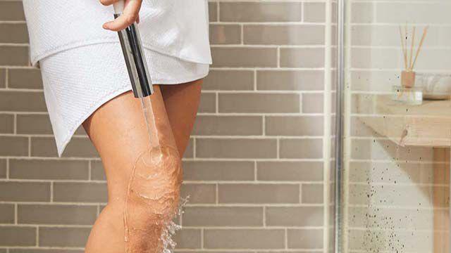 Frau steht in der Dusche und lässt Wasser über ihr Knie laufen, nur die Beine von ihr sind zu sehen.
