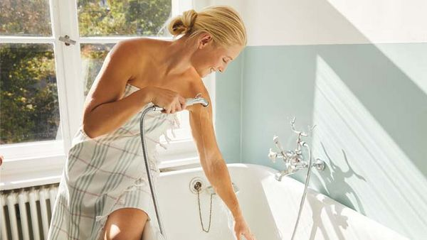 Blonde Frau im Handtuch führt über der Badewanne einen Armguss durch.