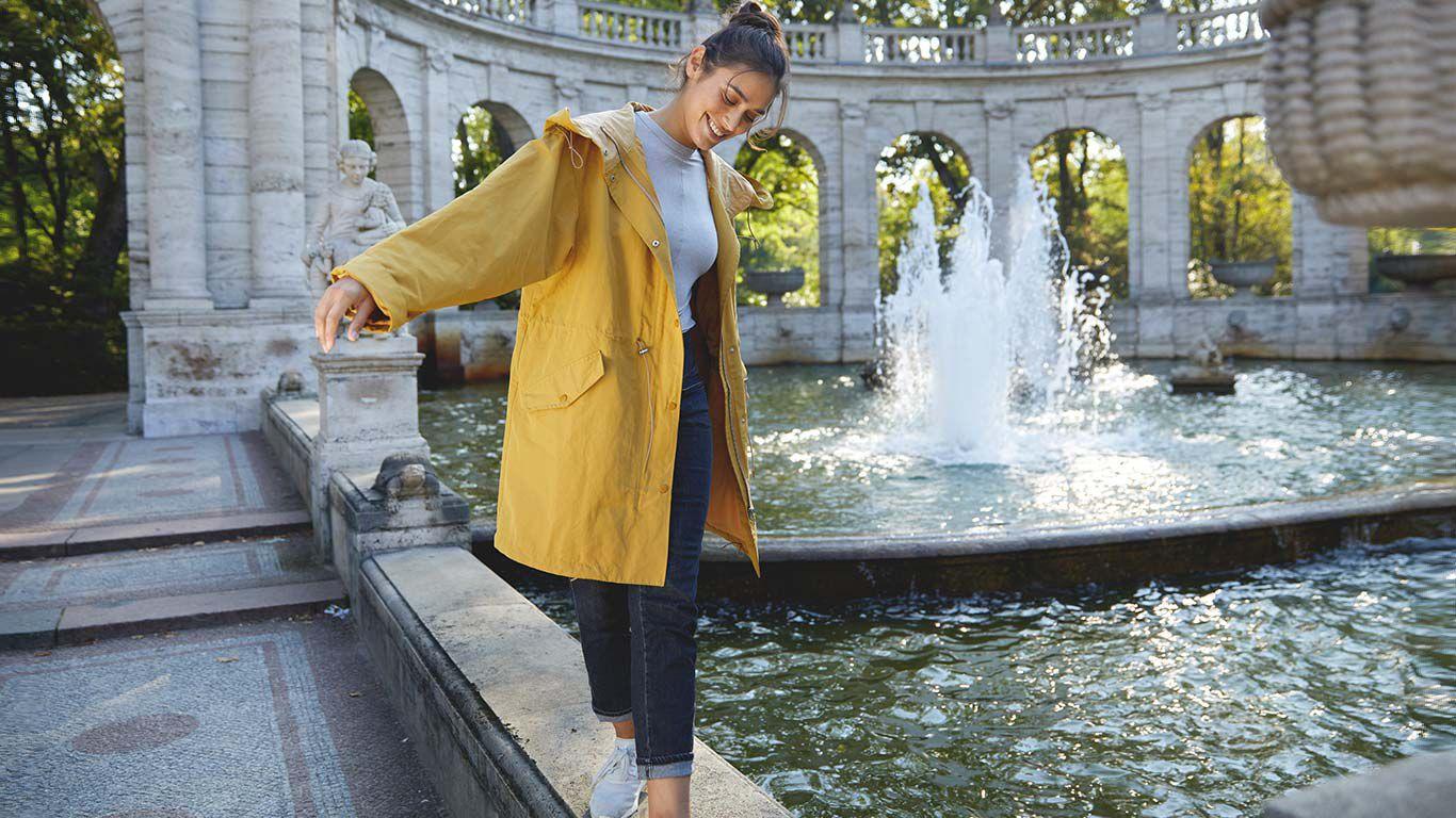 Frau im gelben Regenmantel balanciert auf dem Randstein eines Brunnens.