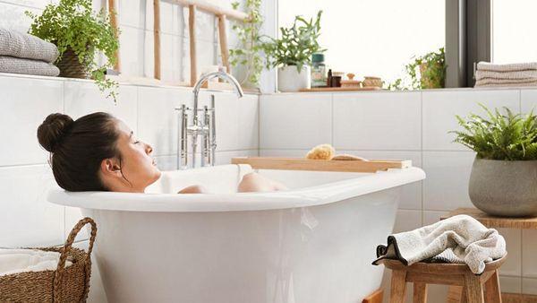 Dunkelhaarige Frau mit Dutt entspannt in der Badewanne.