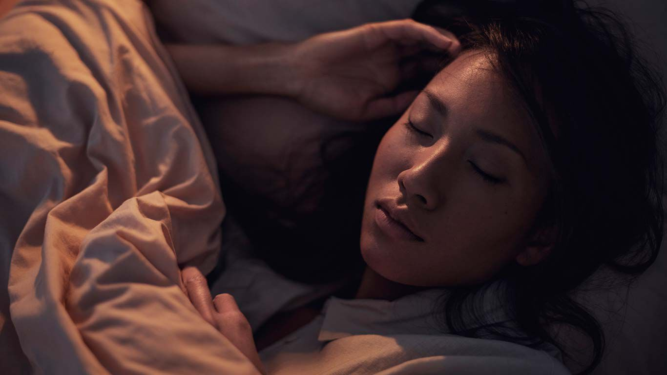 Frau liegt im Bet und schläft.