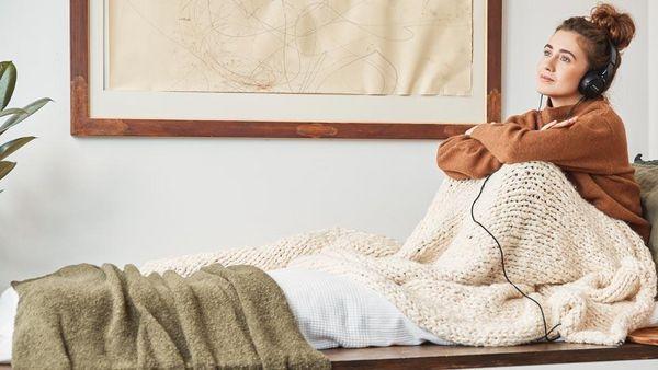 Frau mit Dutt und Kopfhörern sitzt in eine Decke gewickelt auf einer Bank.