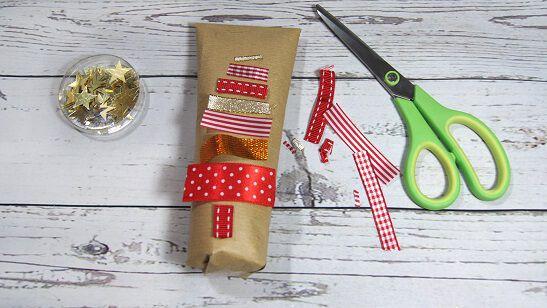 Schritt 2: Klebe die Geschenkband-Stücke auf die Geschenkverpackung