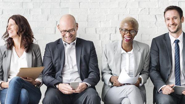 Vier Menschen in Businessklamotten sitzen nebeneinander.