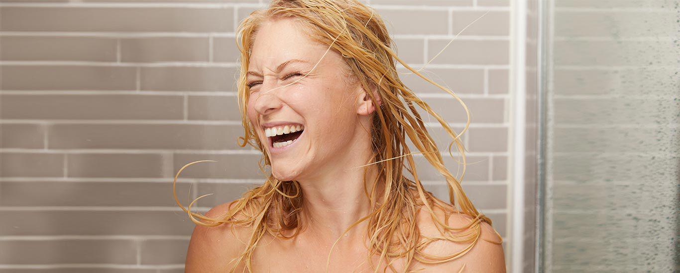 Blonde Frau in der Dusche. Ihre nassen Haare wirft sie lachend um sich.