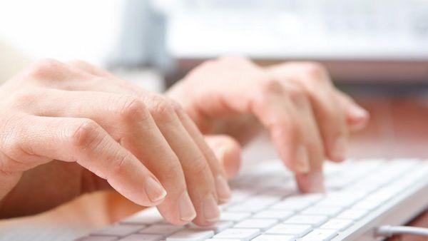 Hände tippen auf Tastatur.