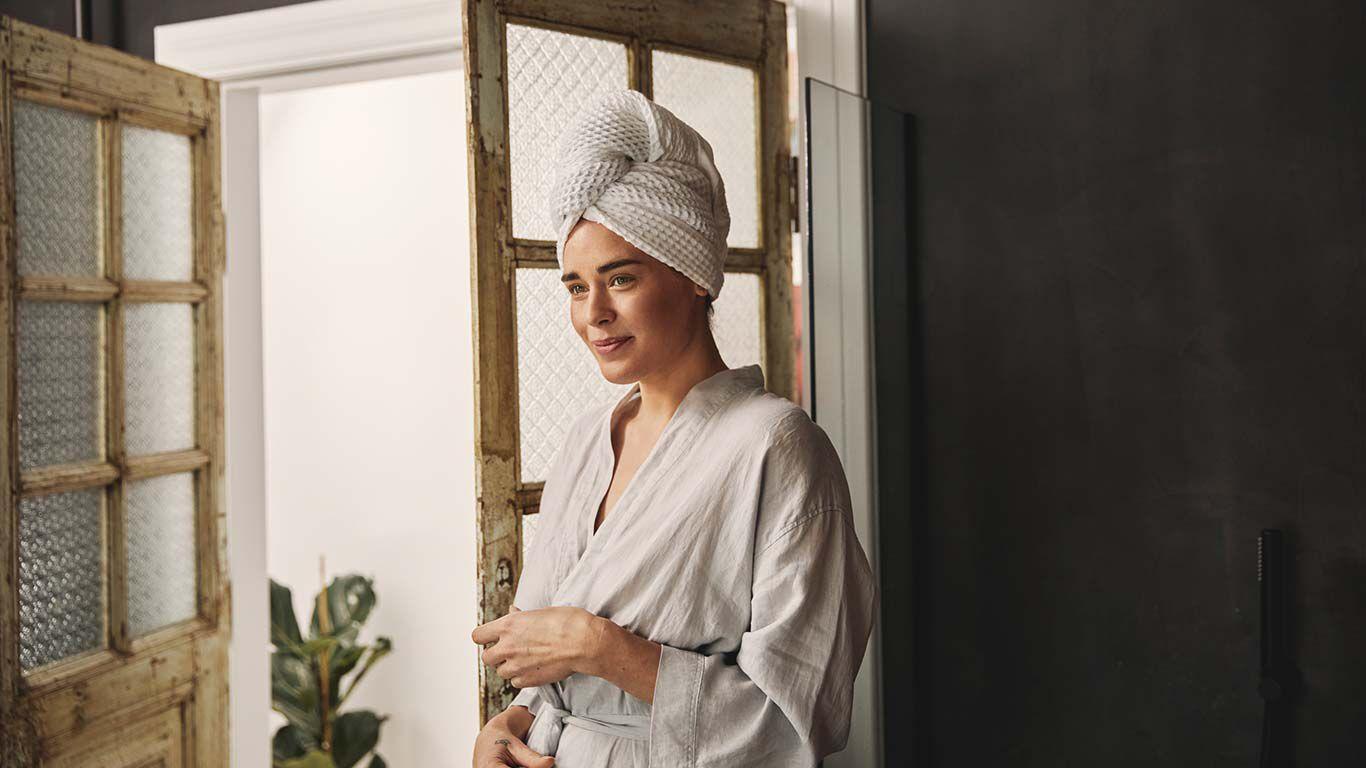 Frau in weißem Bademantel und Turban steht im Badezimmer.