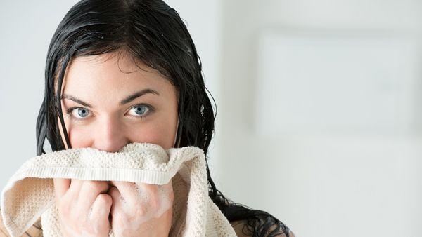 Frau mit nassen Haaren hält sich Handtuch vor ihr Gesicht.