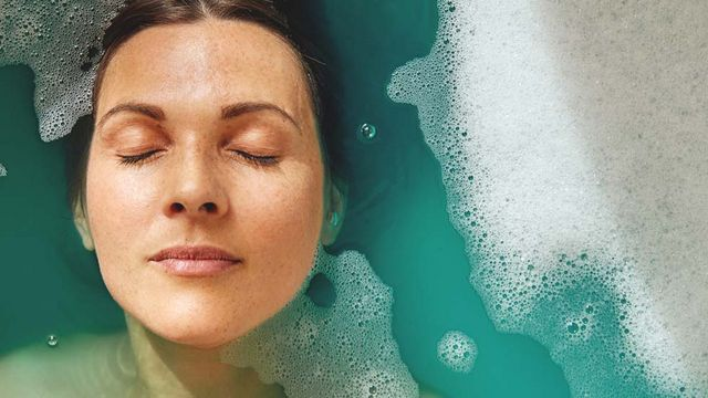 Frau liegt bis zum Haaransatz in einer Badewanne mit blauem Wasser.