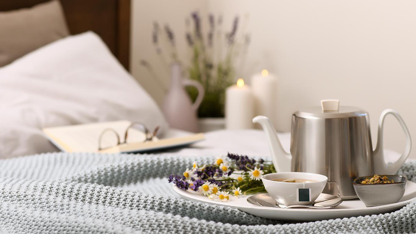 Teekanne und Tasse stehen auf dem Bett