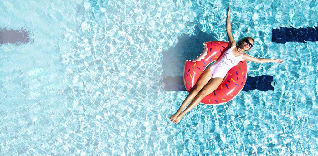 Frau in weißem Badeanzug auf einem Pinken Donut-Schwimmring im Wasser.