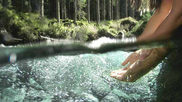 Hände, die in seichtes Wasser gleiten.