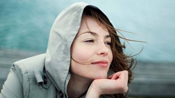 Frau sitzt im Wind und stützt ihr Kinn auf ihrer Hand ab.