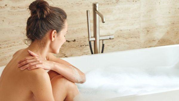 Frau sitzt mit angezogenen Beinen in einer Badewanne.