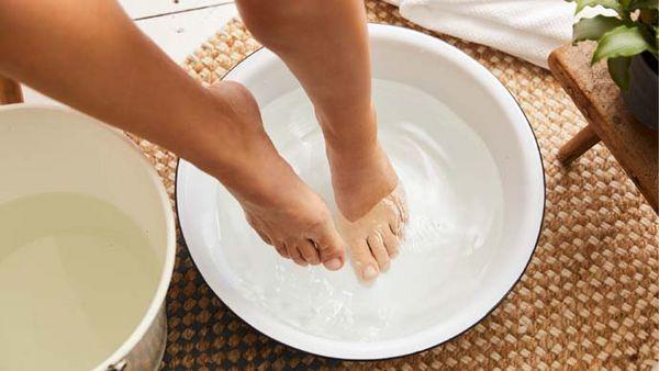 Füße in einem weisen Eimer voll kaltem Wasser. Links daneben ein zweiter Eimer mit warmem Wasser.