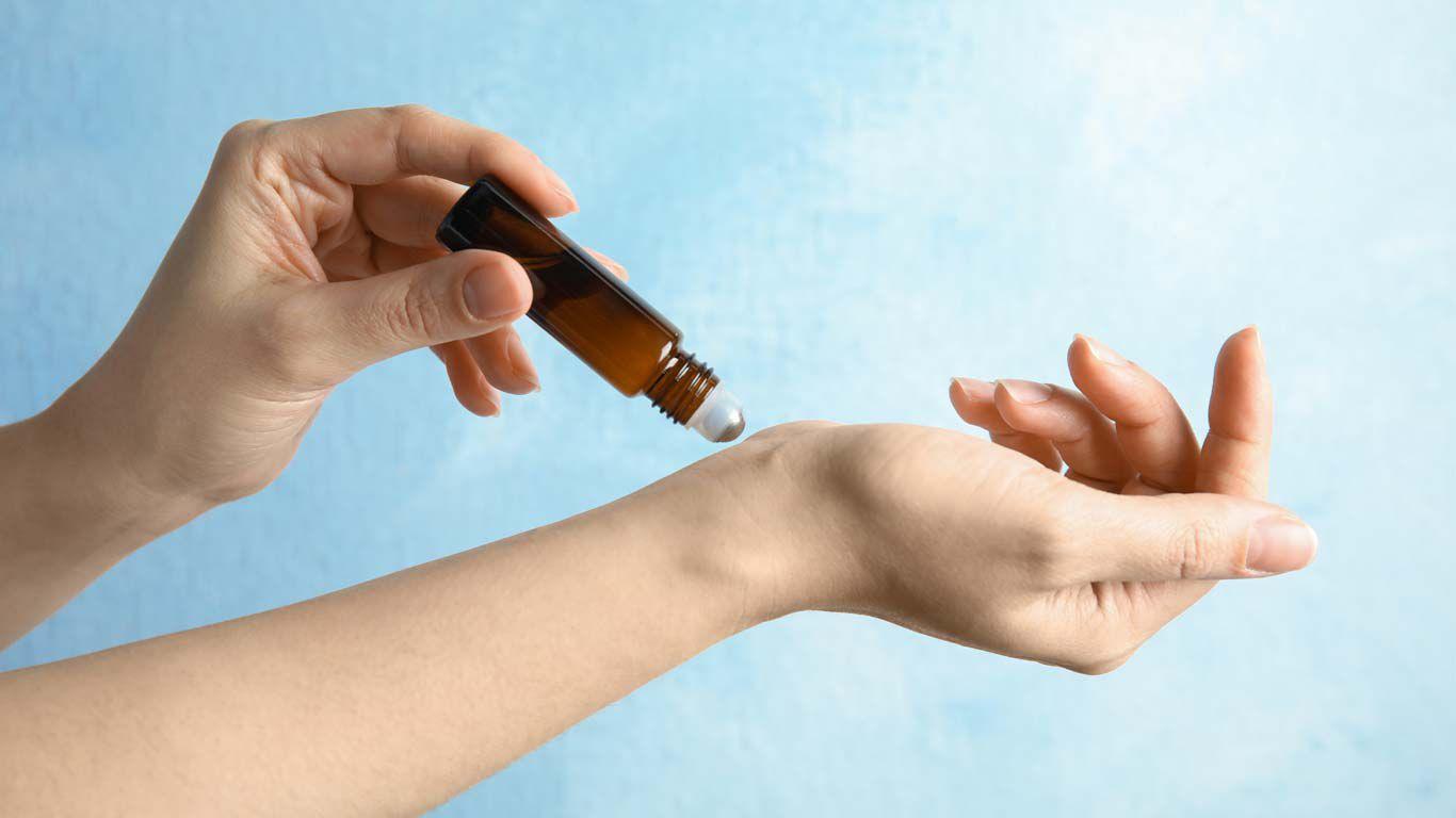Frau benetzt die Haut mit ätherischem Öl