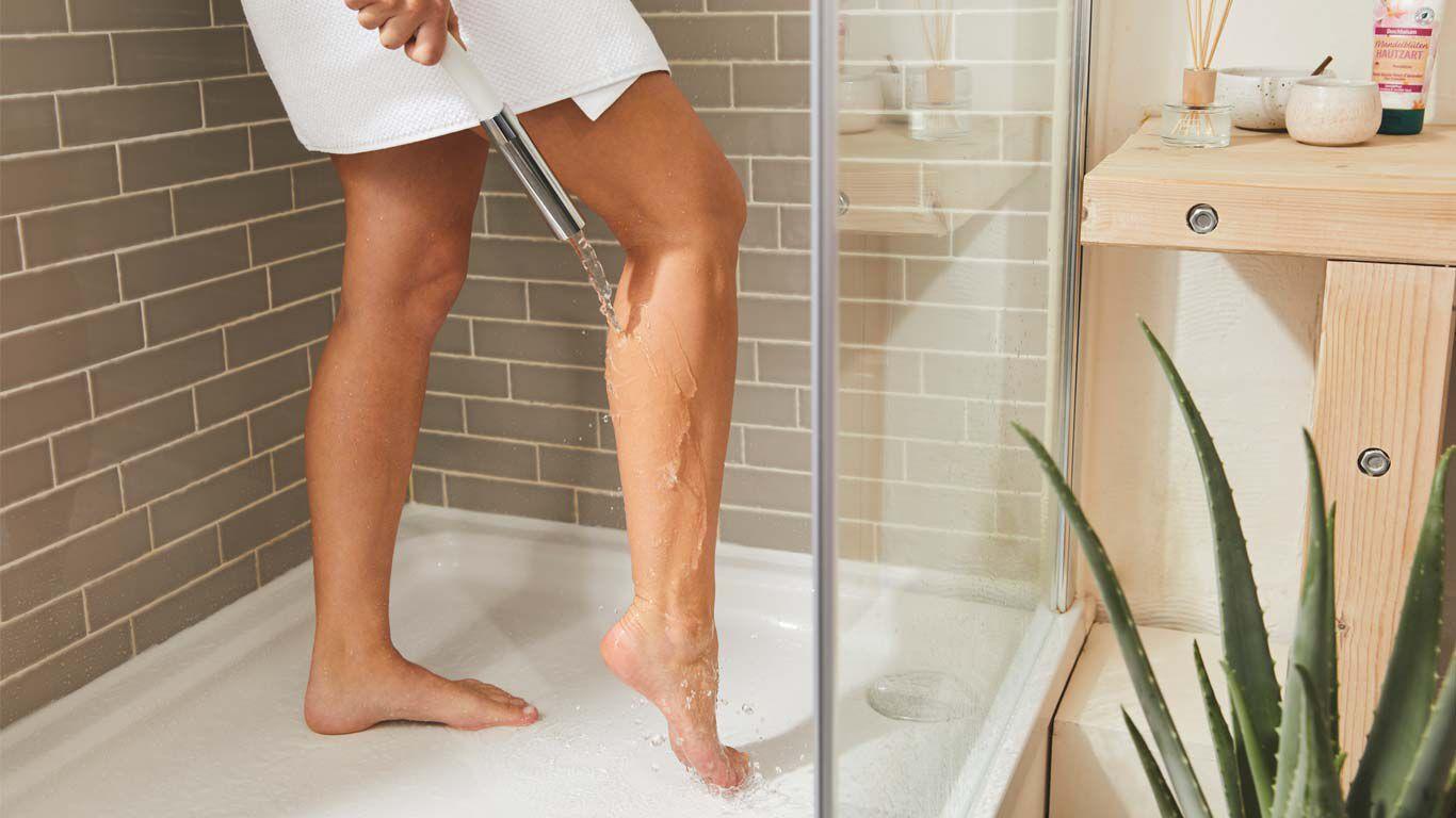 Frau steht in der Dusche und lässt Wasser über die Rückseite des rechten Beines laufen.