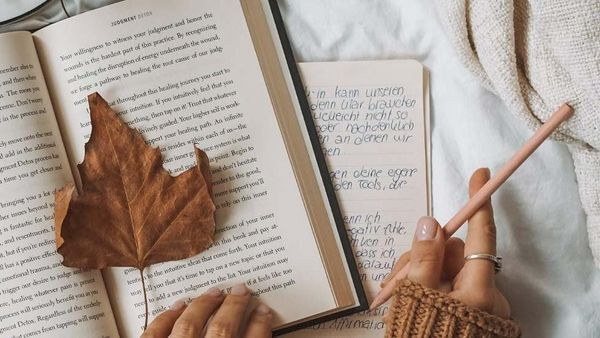 Aufgeschlagene Bücher, darauf ein Herbstblatt und eine Hand, die einen Bleistift hält.