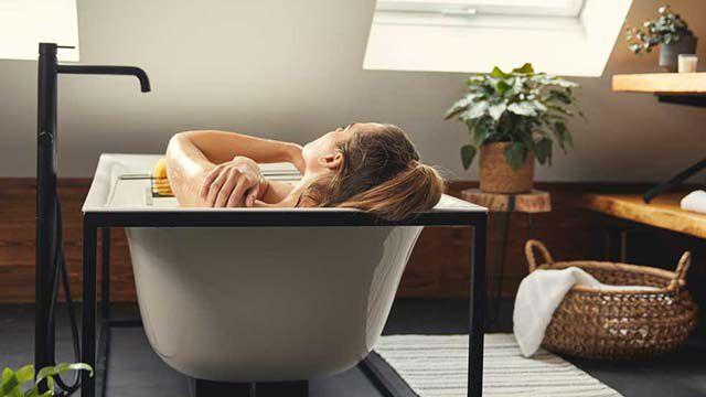 In einem Badezimmer liegt eine Frau in einer Badewanne, man kann sie nur von hinten sehen.