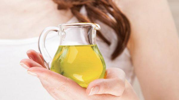 Frau hält Kännchen aus Glas mit Öl.