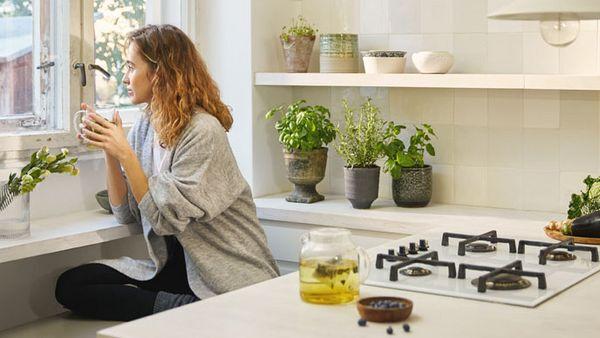 Frau sitzt mit einer Tasse Tee auf einer Bank in der Küche und schaut aus dem Fenster.