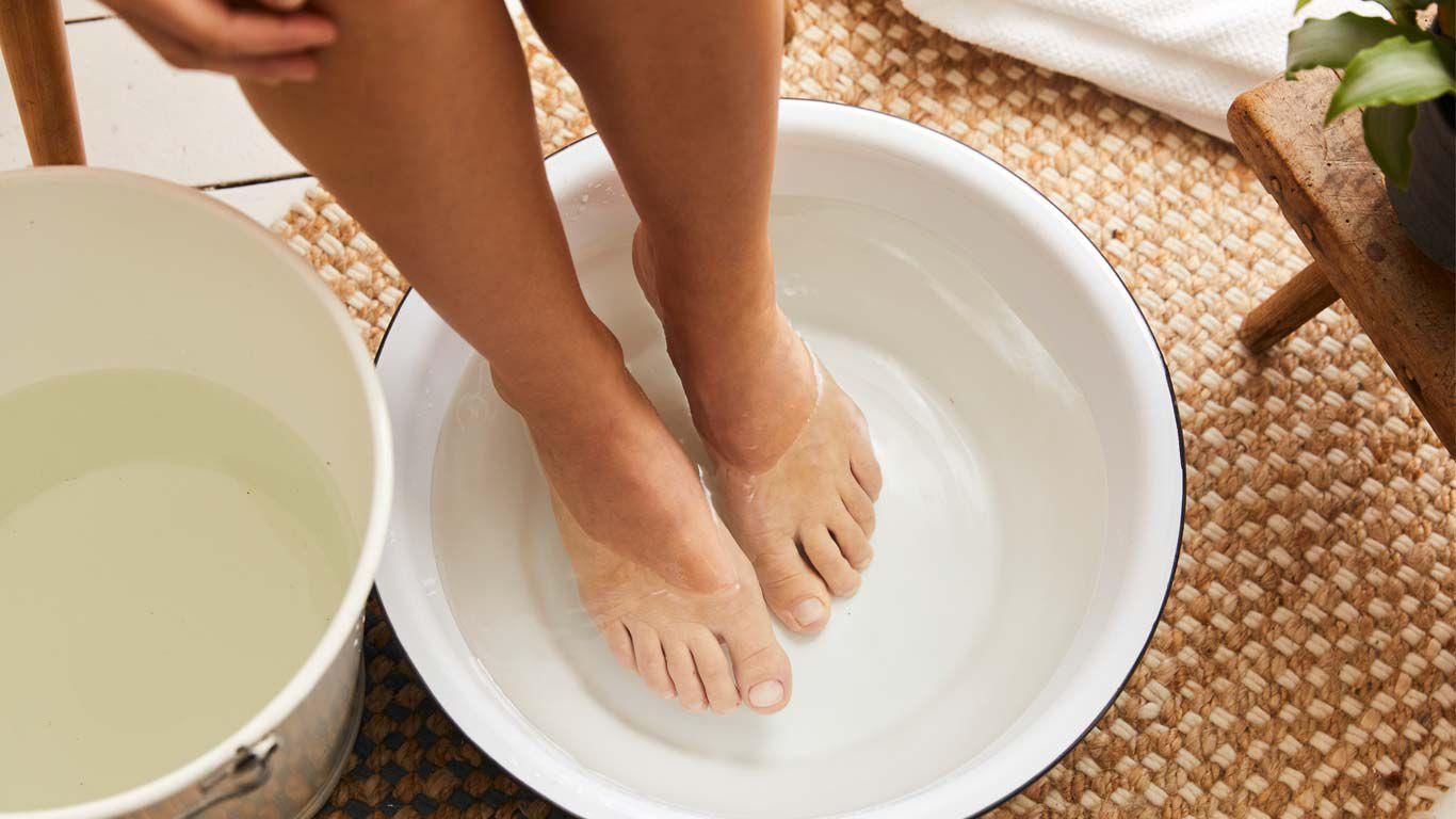 Zwei Füße, die in einer mit Wasser gefüllten Schüssel sind. Daneben ein Eimer mit Wasser.