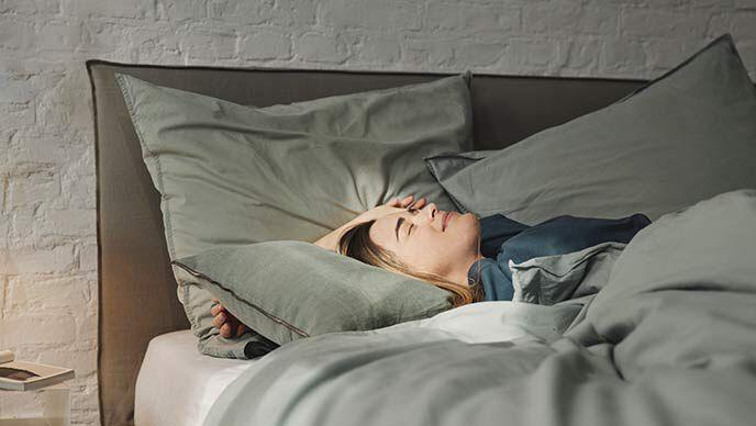 Dunkelhaarige Frau liegt im Bett und genießt Sonnestrahlen auf ihrem Gesicht.